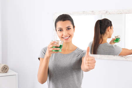 Young woman with mouthwash in bathroom. Teeth and oral care