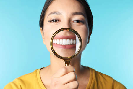 Young woman with healthy teeth and magnifier on color background, closeup