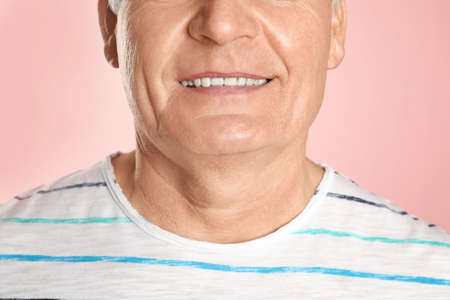 Mature man with healthy teeth on color background, closeup