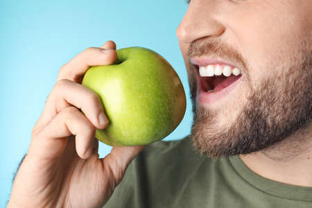 Young man with healthy teeth and apple on color background, closeup