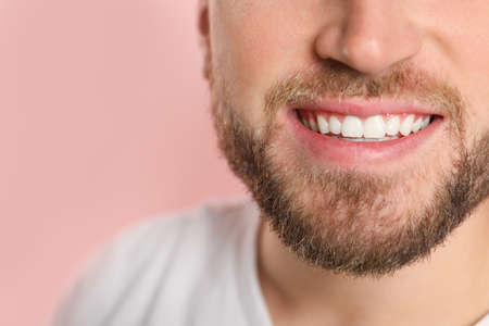 Young man with healthy teeth on color background, closeup. Space for text Imagens