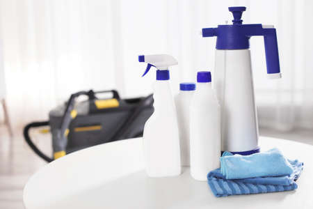 Set of professional cleaning supplies on table indoors. Space for text