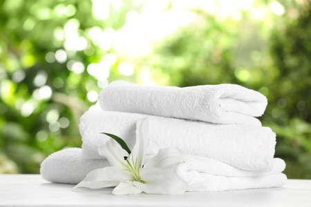 Pila de toallas limpias y suaves y flores en la mesa contra el fondo borroso Foto de archivo