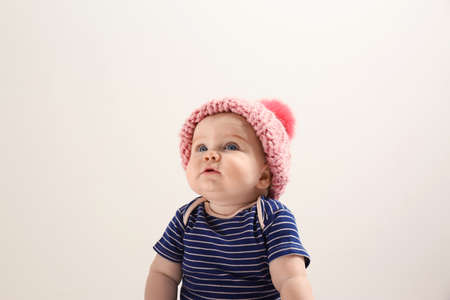 Little child in knitted hat on light background. Baby accessories