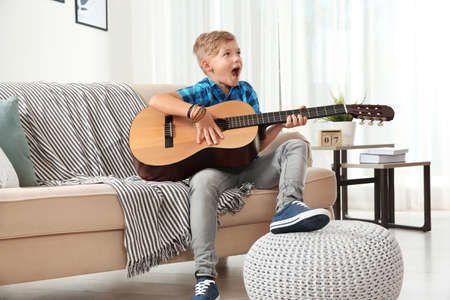 Cute little boy playing guitar on sofa in room