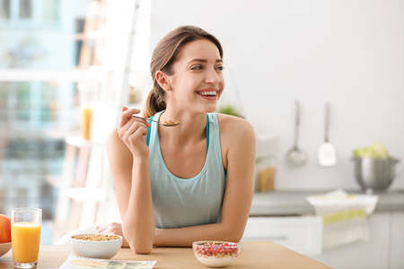 Young woman in fitness clothes having healthy breakfast at home Zdjęcie Seryjne