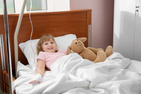 Little child with intravenous drip and toy in hospital bed Stock Photo