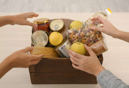 Women taking food out of donation box on wooden table, closeup Banco de Imagens - 117713457