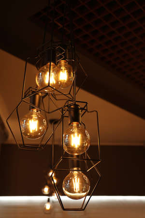Pendant lamps with glowing light bulbs indoors