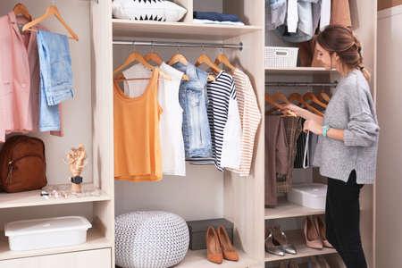 Donna che sceglie l'abito da un grande armadio guardaroba con vestiti alla moda, scarpe e cose per la casa