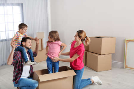 Happy family playing with cardboard box in their new house. Moving day Foto de archivo - 117993979