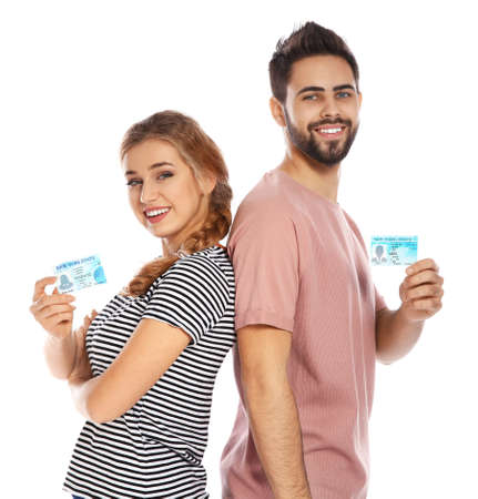 Happy young people with driving licenses on white background