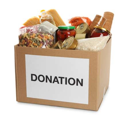 Boîte de dons pleine de produits différents sur fond blanc Banque d'images