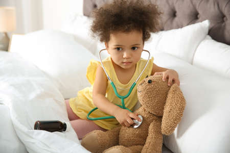 Cute African American child imagining herself as doctor while playing with stethoscope and toy bunny at home Banque d'images