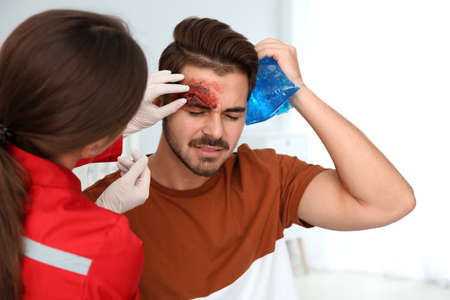 Nurse examining young man's head injury in clinic. First aid concept