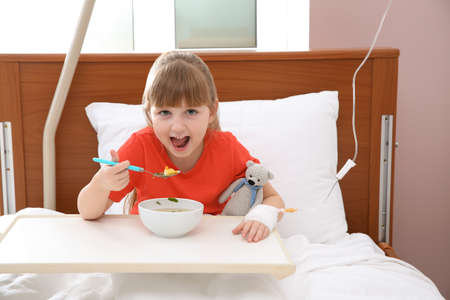 Little child with intravenous drip eating soup in hospital bed