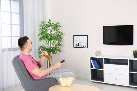 Handsome young man watching TV in armchair at home Imagens