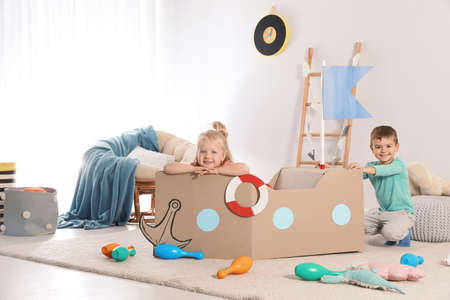 Cute little children playing with cardboard ship at home