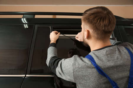 Skilled worker tinting car window in shop