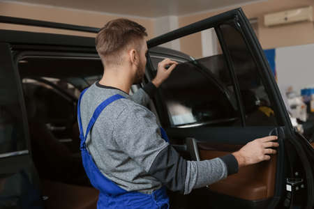 Skilled worker checking tinted car window in shop
