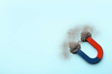 Magnete con polvere di ferro su sfondo colorato, vista dall'alto. Spazio per il testo