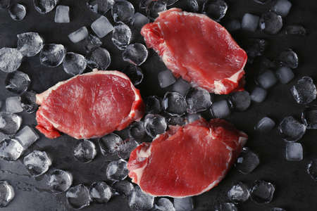 Flat lay composition with raw meat and ice cubes on dark background