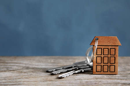 House keys with trinket on wooden table against color background. Space for text