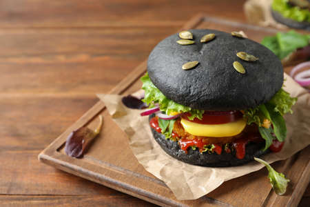 Board with tasty black vegetarian burger on wooden table