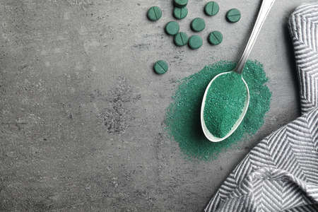 Spoon of spirulina powder and pills on grey background, top view with space for text Stock Photo