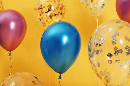 Bright balloons with ribbons on color background