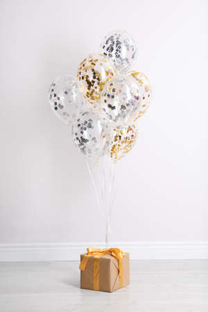 Bright balloons and gift box on floor against white wall