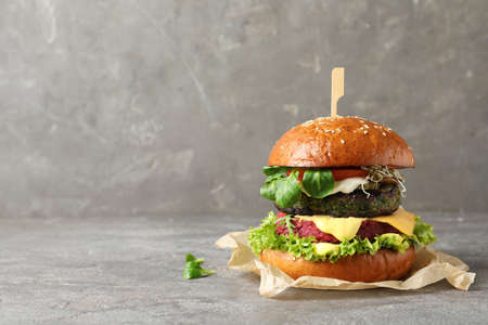 Vegan burger with beet and falafel patties on table against grey background. Space for text