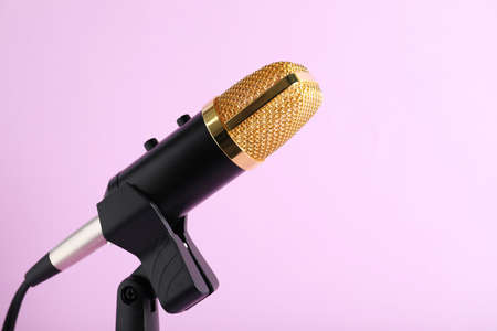 Condenser microphone on color background, space for text
