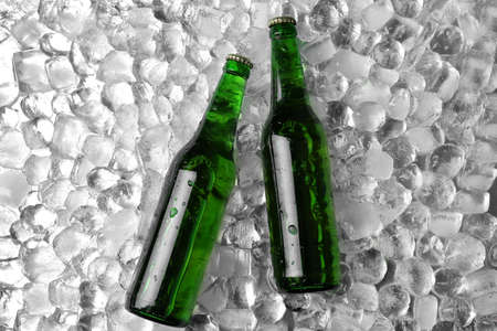 Bottles of beer on ice cubes, flat lay