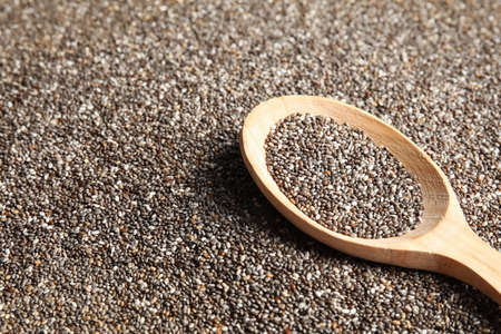 Spoon of chia seeds on grains, closeup. Space for text