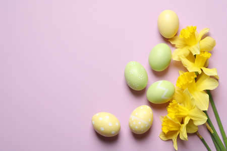 Flat lay composition of painted Easter eggs and flowers on color background, space for text