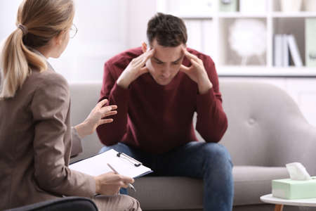 Psychotherapist working with young man in office