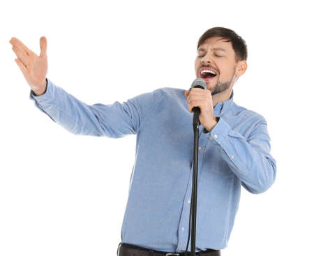 Handsome man singing in microphone on white background