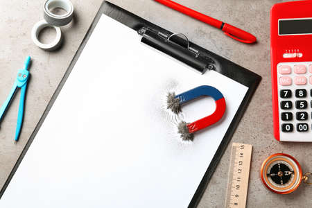 Clipboard, stationery and magnet with iron powder on table, top view. Space for text