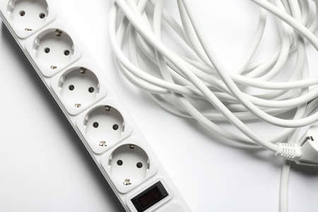 Extension cord on white background, top view. Electrician's equipment