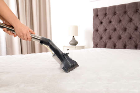 Woman disinfecting mattress with vacuum cleaner, closeup. Space for text Stock Photo