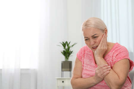 Mature woman suffering from strong tooth pain at home, space for text