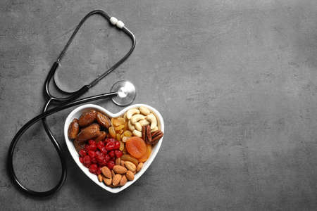Heart shaped bowl with nuts and dried fruits near stethoscope on grey background, top view. Space for text