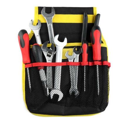 Bag with different construction tools on white background, top view