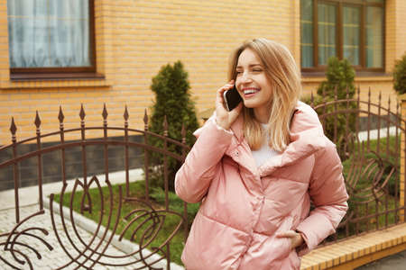 Young woman talking on mobile phone outdoors. Space for text