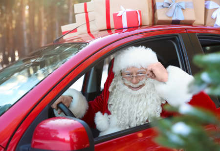 Authentic Santa Claus driving car with gift boxes, view from outside