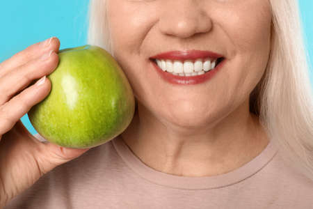 Smiling woman with perfect teeth and green apple on color background, closeup