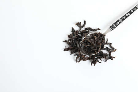Spoon with Da Hong Pao Oolong tea on white background, top view