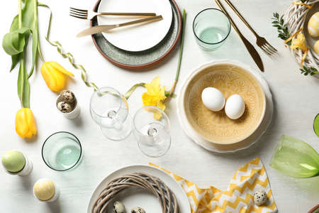 Festive Easter table setting with eggs on wooden background, top view
