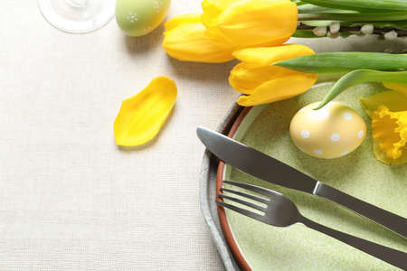 Festive Easter table setting with flowers on light background, top view. Space for text